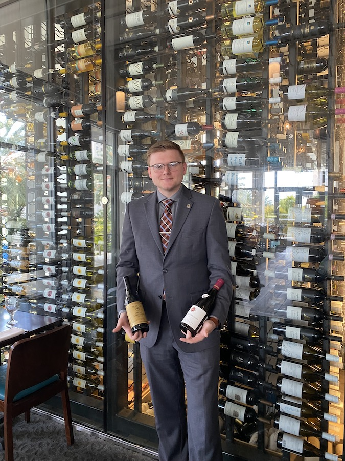 Certified Sommelier Ryan McSwiggin next to our <br/> 22 foot wine tower.